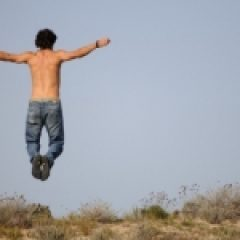 Man jumping at beach for short term health insurance